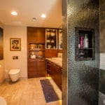 master bathroom with floating toilet and floating cabinets in dark wood