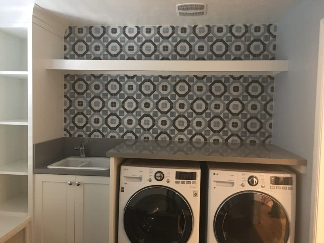 laundry room, washer and dryer with blue wallpaper behind and white shelf. white cabinets