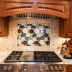 Large mosaic over a stove with cabinets over the stove