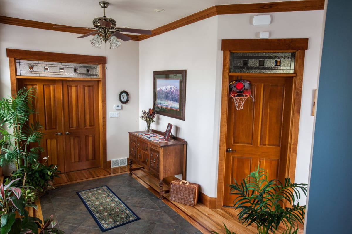 Foyer with double doors on left and a single door on the right. lots of plants