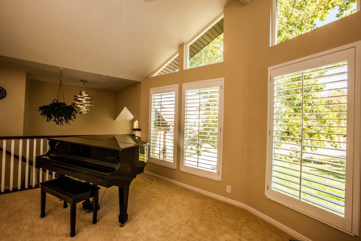 piano room with a grand piano with a stairway behind it. Large open windows on the right wall