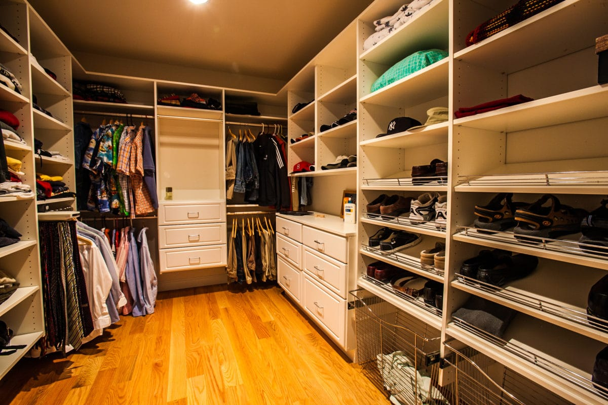large walk-in closet with shelving, drawers and a wood floor