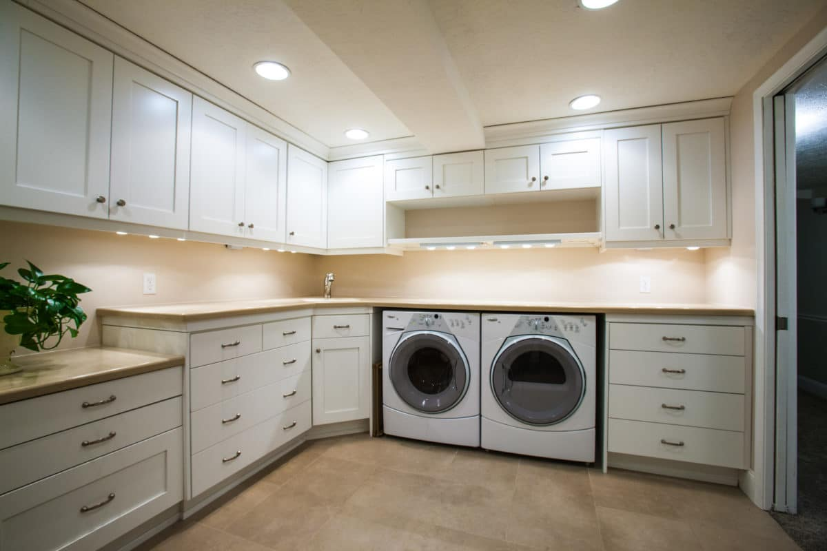 classic white cabinets in laundry room uppercabinets and front loading washer and dryer wood floor