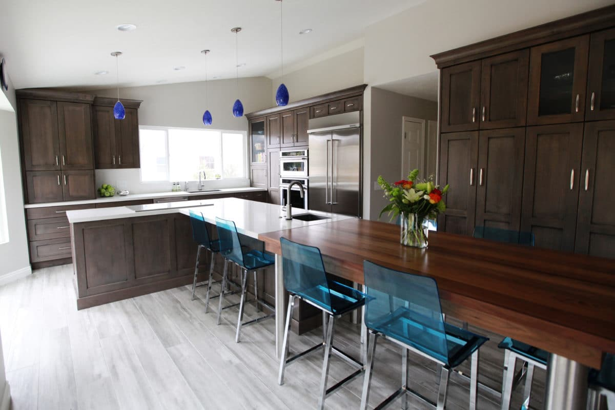 Dark wooded kitchen, with white flooring and a large table on the right.