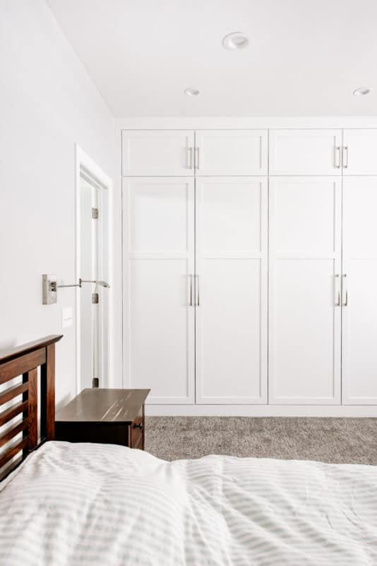 wall of white cabinets in master bedroom suite floor to ceiling cabinets