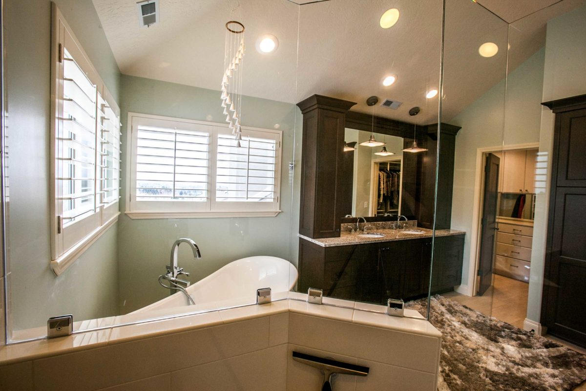 mint walled bathroom from inside a shower with view of cabinets and bathtub