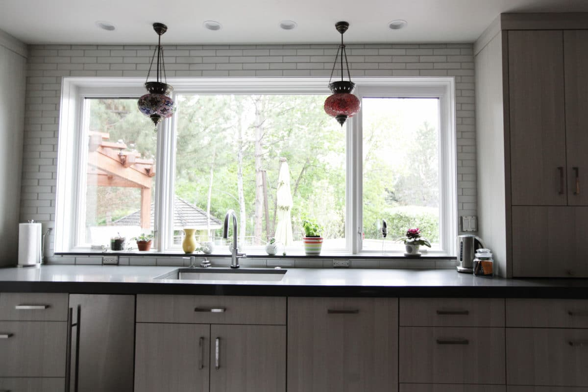 large window, with gray cabinetry and dark countertops.