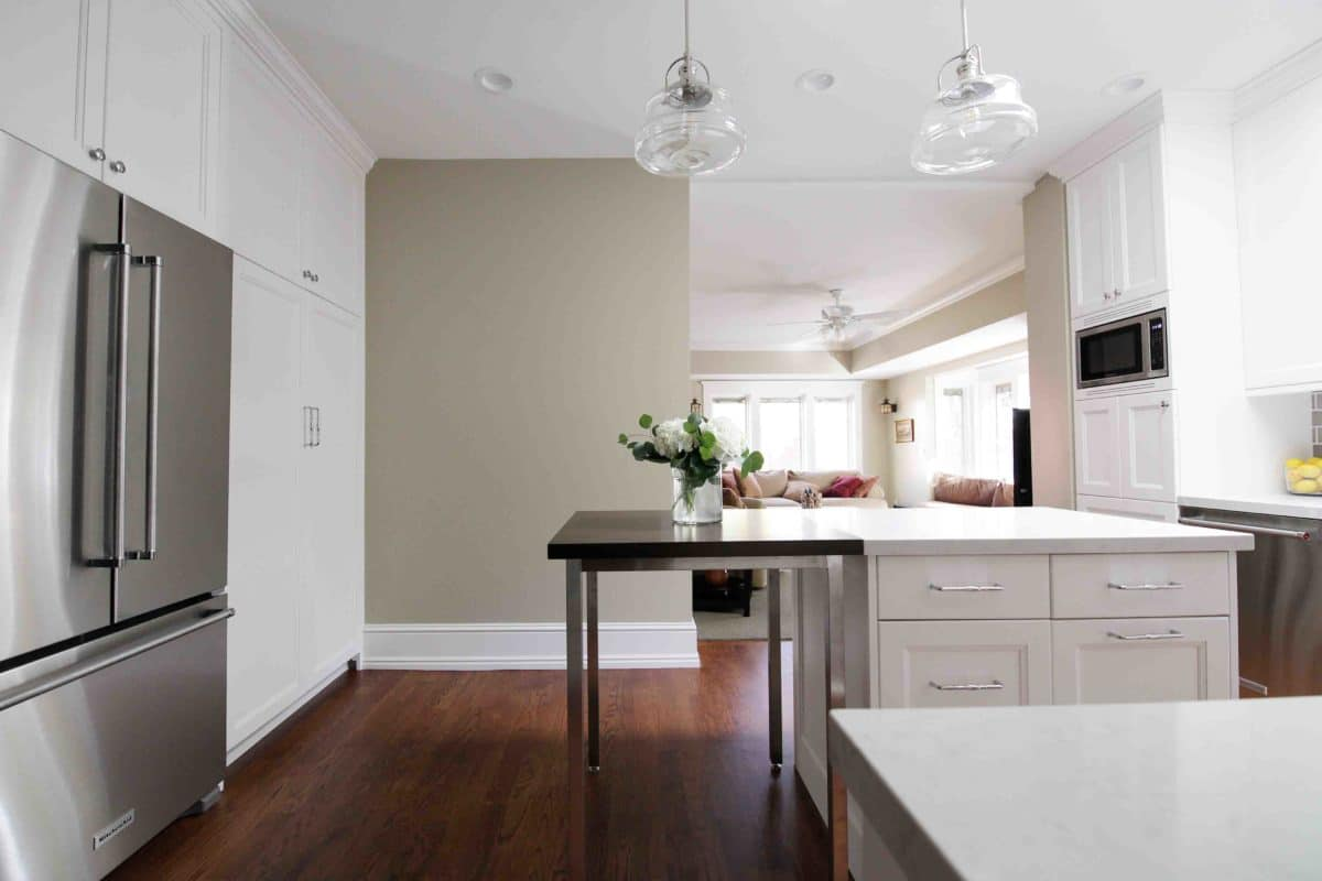 White kitchen cabinets with olive wall, table integrated into island cabinets