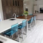 blue chairs on a large wood kitchen table and island.