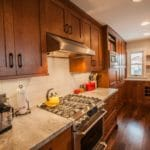 wood cabinets and granite and silver stove