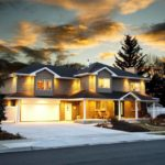 exterior home remodel, colonial style, lighted in front of sunset