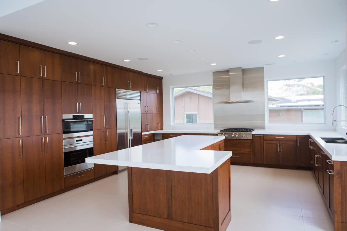 Large u shaped kitchen with island in the center. double oven. stainless hood and other appliances