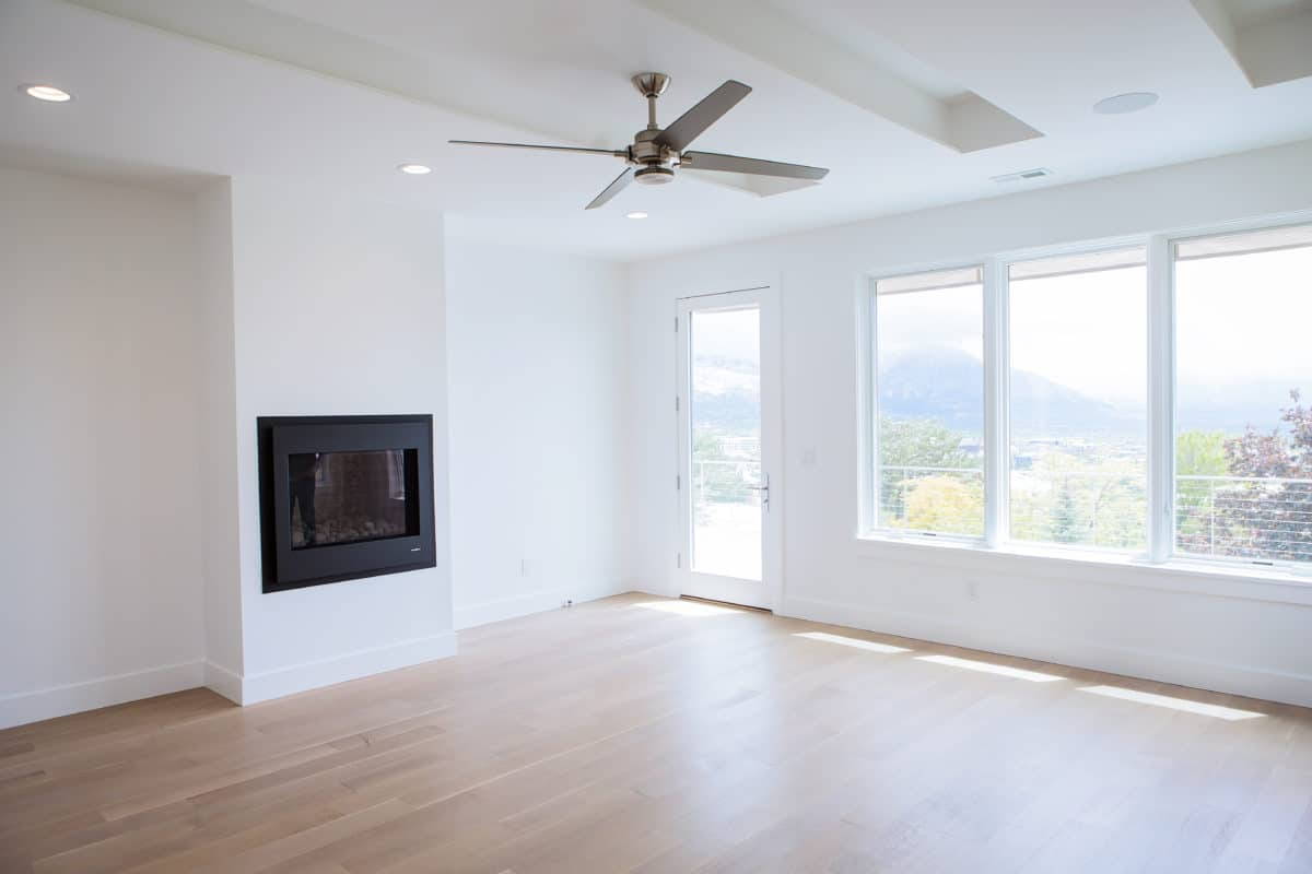 great room of new custom home fireplace with minimal hearth large ceiling fan, windows and door to outside and white paint
