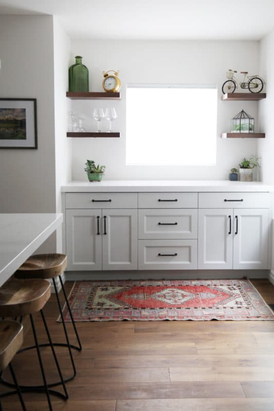 white kitchen cabinets with wood floating shelves around a window. wood floors