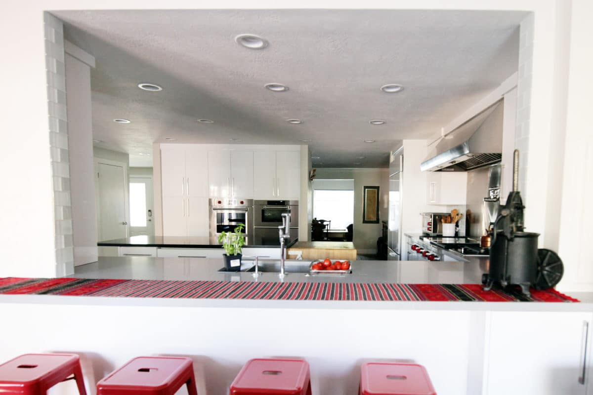 white kitchen cabinets, stainless appliances sink and red accents