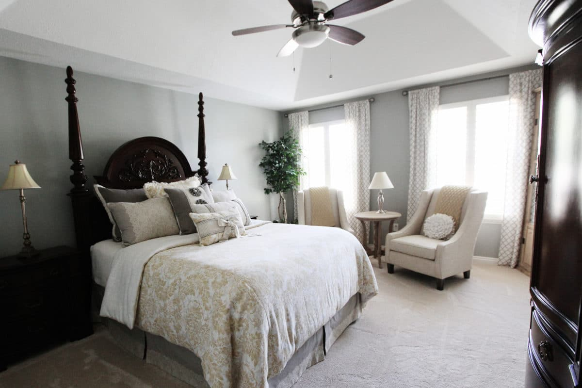 master bedroom with chairs for sitting area, fan blue grey walls, white curtains