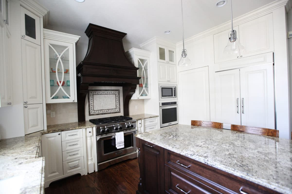 kitchen with oven and microwave built in, dark wood hood and island cabinets, white wall cabinets