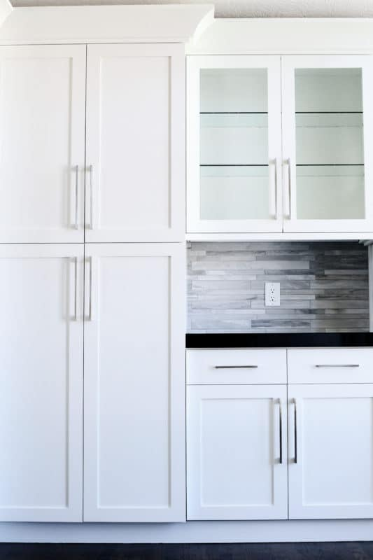 white pantry cabinet and kitchen cabinets, dark counter top