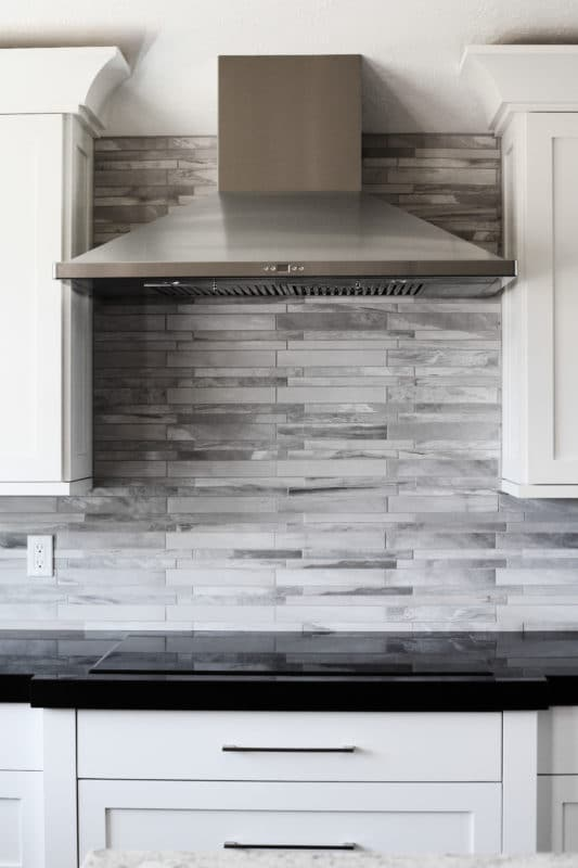 stack style tile backsplash and stainless vent hood white cabinets with dark countertop