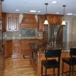 kitchen remodel wood cabinets, island with sink and microwave, tile backsplash. stainless steel appliances.