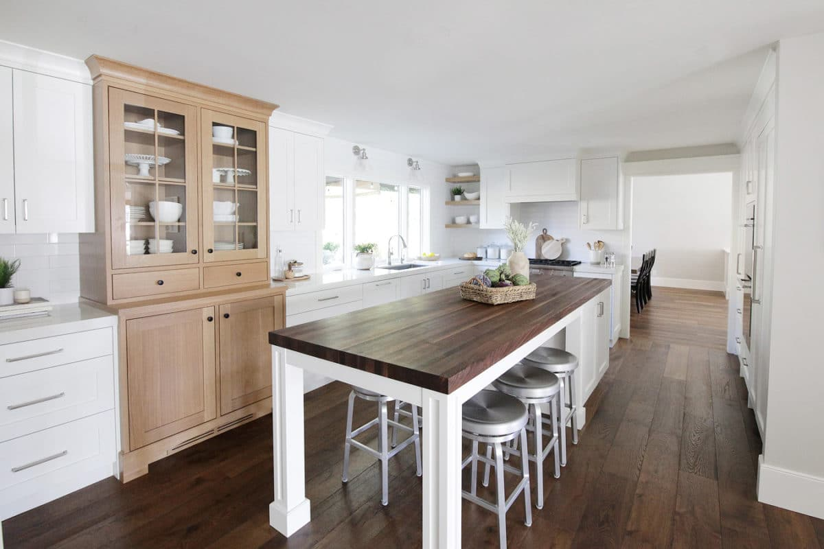 kitchen with white and natural cabinets darker wood counter top on integrated kitchen table and island, silver barstools below. white kitchen cabinets wood grain flooring