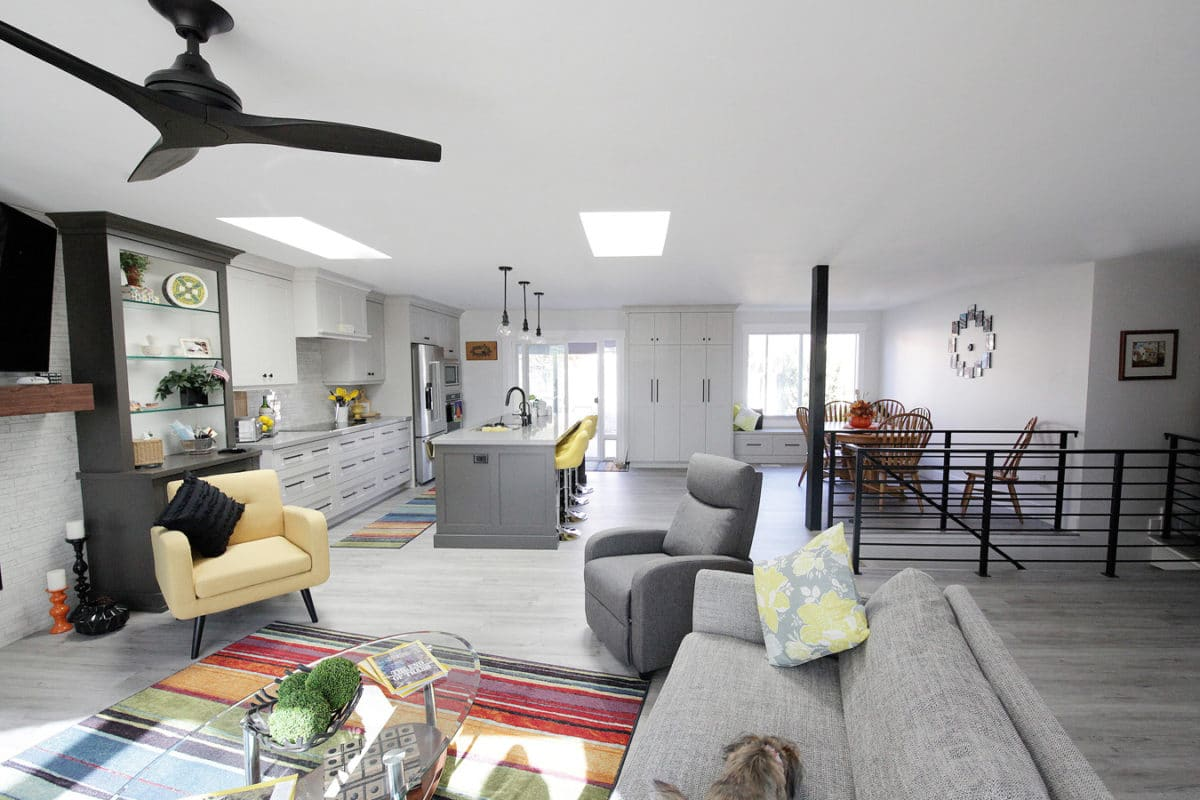 kitchen remodel fan, sliding glass door, stainless steel appliances, metal stair rail, gray and yellow furniture. floor to ceiling cabinets for pantry. stacked tile on fireplace and backsplash wood like gray tile floor